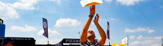 Man throwing pizza dough into the air