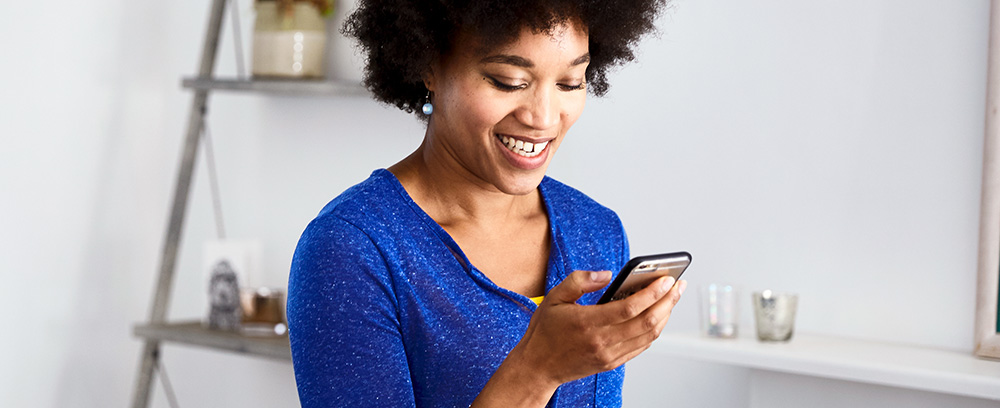 Woman smiling, whilst researching balance transfers on her mobile phone