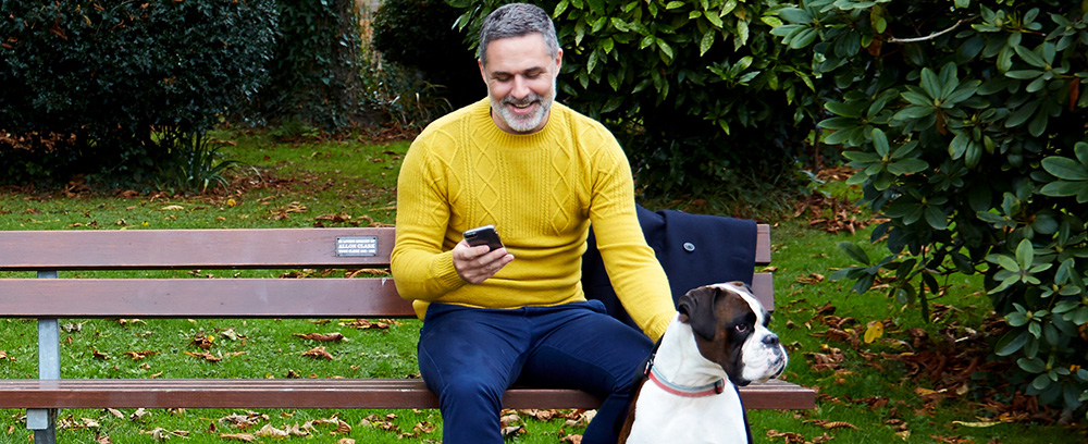Man sat on the bench with his dog beside him, checking his bank details on his mobile phone