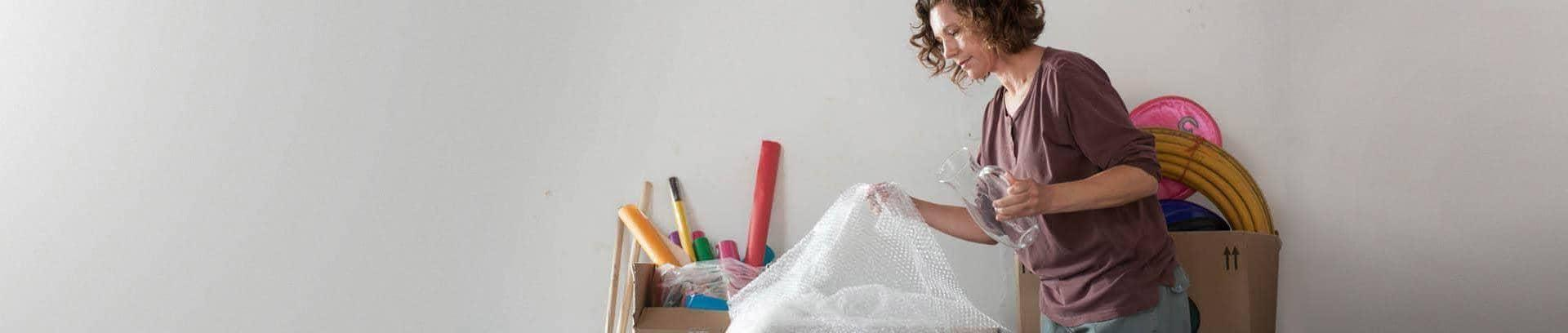 Woman packing a vase in bubble wrap, ready to move house