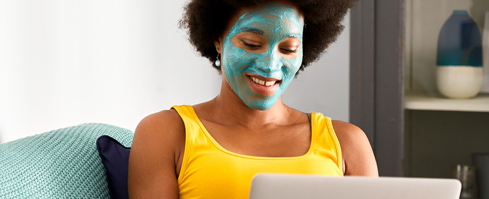 A young woman, relaxing with a face mask on, browsing credit cards online