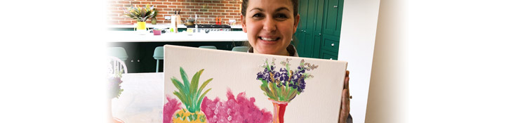 Giovanna holding a hand painted painting of flowers