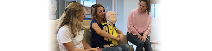 Giovanna watching a young lady perform CPR on a dummy.