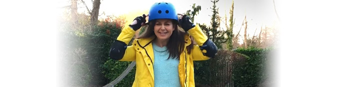 Giovanna with a yellow jacket and blue skateboarding helmet on