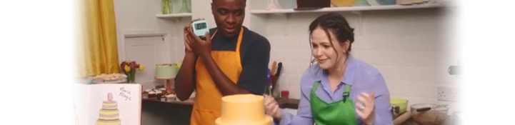 Giovanna decorating a cake with Liam from the Great British Bake Off