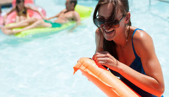 Smiling lady in a pool with a flotation device