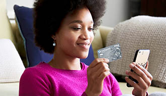 Woman holding her mobile in one hand and credit card in another